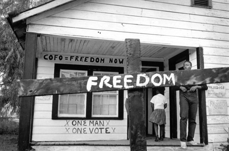 After the Ku Klux Klan burned this cross in front of a Mississippi Delta Freedom House, a civil rights worker transformed it with a painted message.  Tamio Wakayama  Indianola, Mississippi, 1964