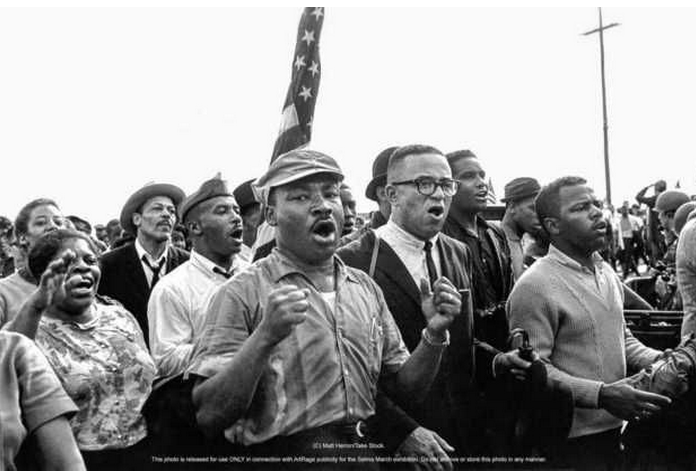 Matt Herron photograph of the Rev.Martin Luther King Jr. leading singing marchers from Selma to Montgomery